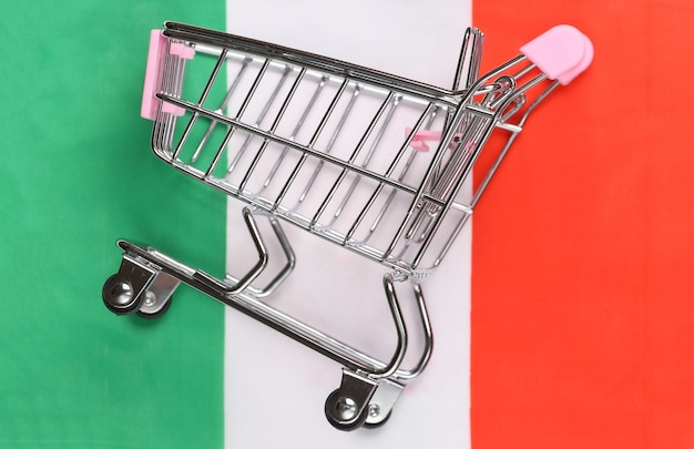 Mini supermarket trolley on blurred italy flag background. shopping concept.
