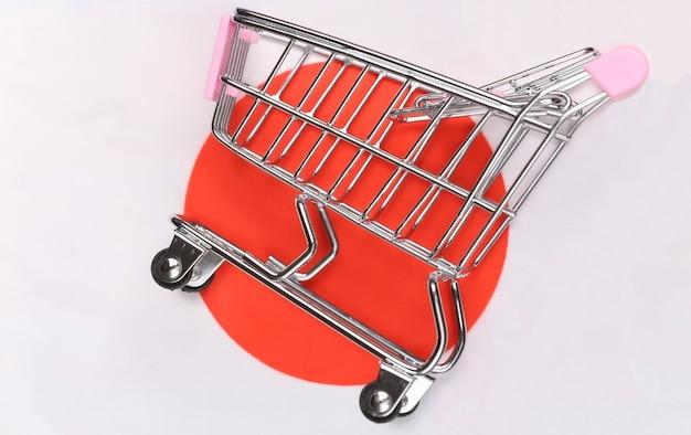 흐리게 일본 국기 배경에 미니 슈퍼마켓 트롤리입니다. 쇼핑 개념.