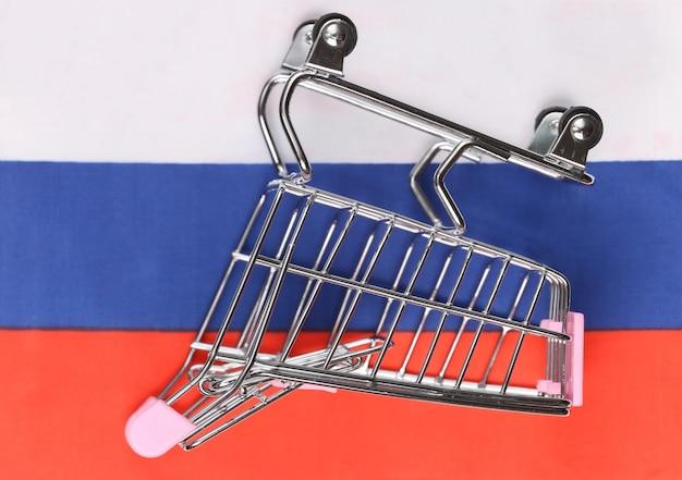 Мини-тележка супермаркета на размытом фоне российского флага. концепция покупок.