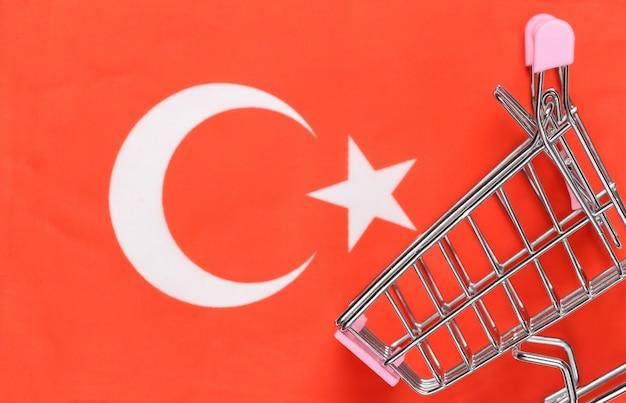 흐리게 터키 국기 배경에 미니 슈퍼마켓 트롤리입니다. 쇼핑 개념.