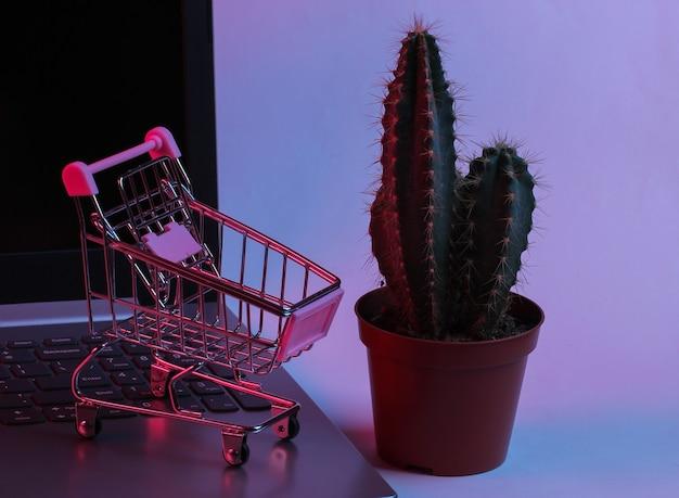 선인장과 노트북 키보드에 미니 슈퍼마켓 트롤리. 네온 그라데이션 빨강-파랑, 자외선. 온라인 쇼핑