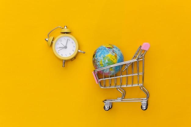 노란색 배경에 글로브와 복고풍 알람 시계가 있는 미니 슈퍼마켓 트롤리