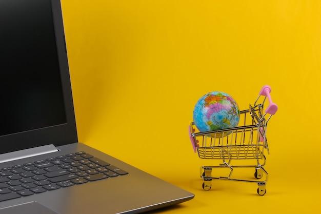 글로브, 노란색 배경에 노트북 미니 슈퍼마켓 트롤리. 온라인 글로벌 쇼핑