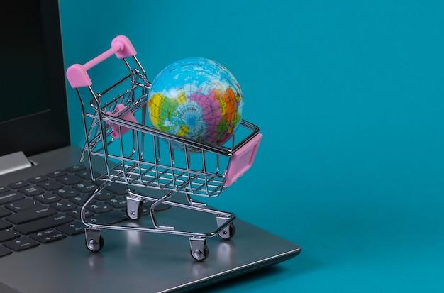 노트북 키보드에 세계와 미니 슈퍼마켓 트롤리입니다. 파란색 배경입니다. 온라인 쇼핑