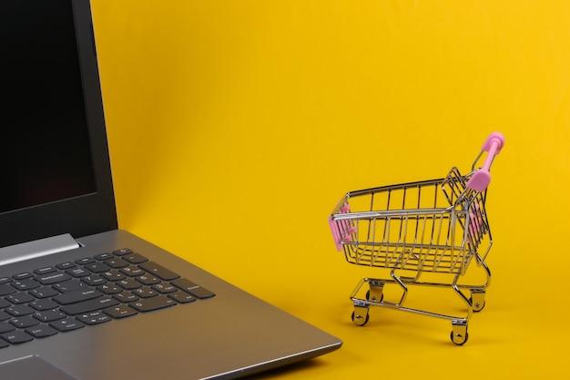 노란색 바탕에 노트북과 미니 슈퍼마켓 트롤리입니다. 온라인 쇼핑