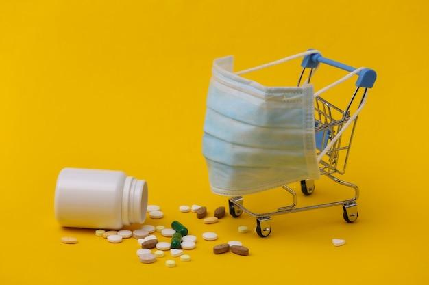 의료용 마스크가 있는 미니 슈퍼마켓 트롤리, 노란색 배경에 알약. 코로나 19 감염병 세계적 유행