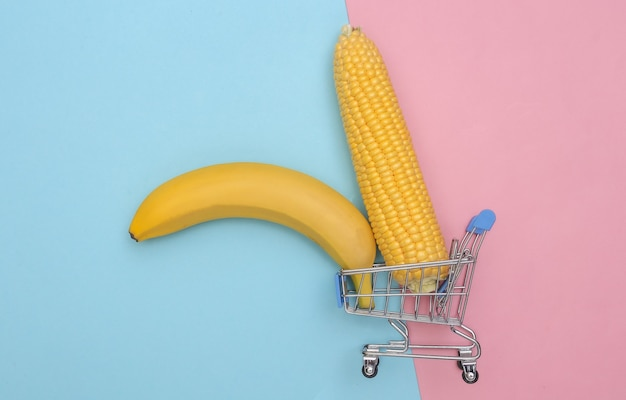Мини-тележка для супермаркета с качелями из кукурузы и банана на розово-голубом пастельном фоне.