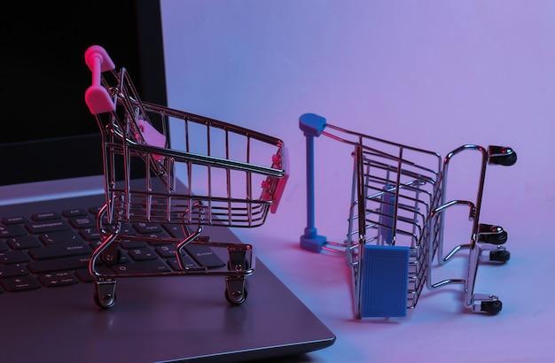 노트북 키보드에 미니 슈퍼마켓 트롤리. 네온 그라데이션 빨강-파랑, 자외선. 온라인 쇼핑