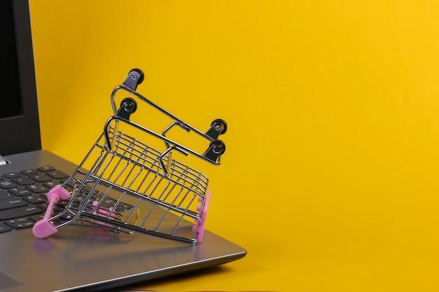 노트북 키보드에 미니 슈퍼마켓 트롤리. 노란색 배경. 온라인 쇼핑