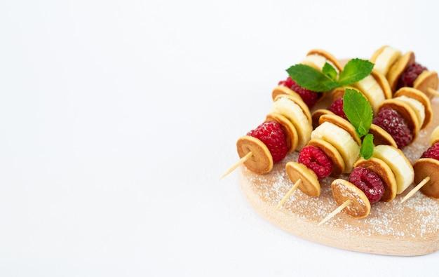 Mini sweet skewers or canape with pancake, raspberry and banana