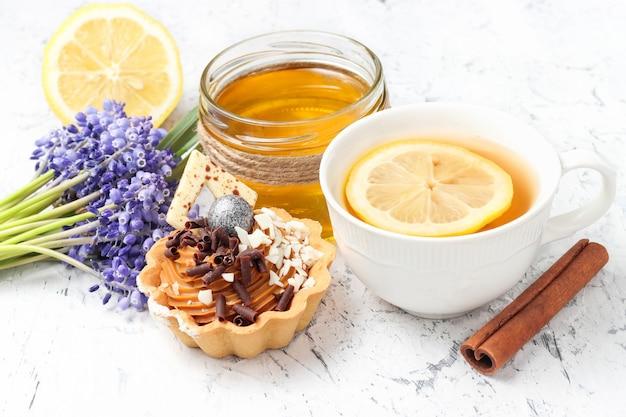 チョコレートとシナモンと蜂蜜とレモンティーのカップで飾られたバスケットのミニタルトケーキ