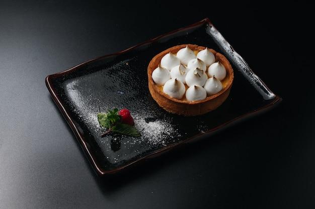 Mini tartlet with fruit jam and meringue tart with italian meringue and cream on black plate homemade desert beautiful breakfast