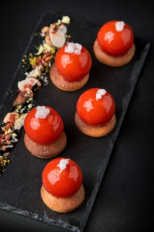 Mini tartlets from berries glazed on top beautifully laid out on a black plate.