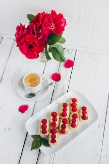 Mini tartlets with cottage cheese and fresh raspberries and a cup of coffee