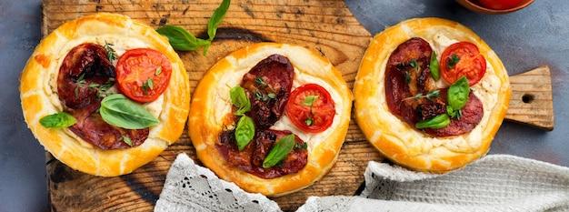 Мини-пироги с вяленым мясом, помидорами, рикоттой, тимьяном, базиликом и оливками на сером фоне бетона. деревенский стиль. выборочный фокус. вид сверху