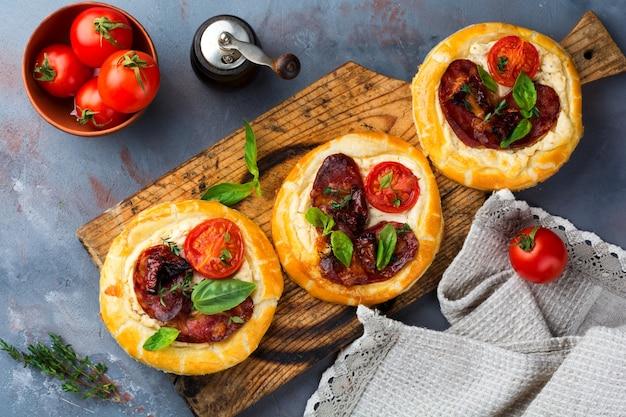 회색 콘크리트 위에 말린 고기, 토마토, 리코 타, 타임, 바질, 올리브가 들어간 미니 타르트