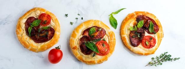 Мини-пироги с вяленым мясом, помидорами, рикоттой, тимьяном, базиликом и оливками на светлом фоне. выборочный фокус. вид сверху