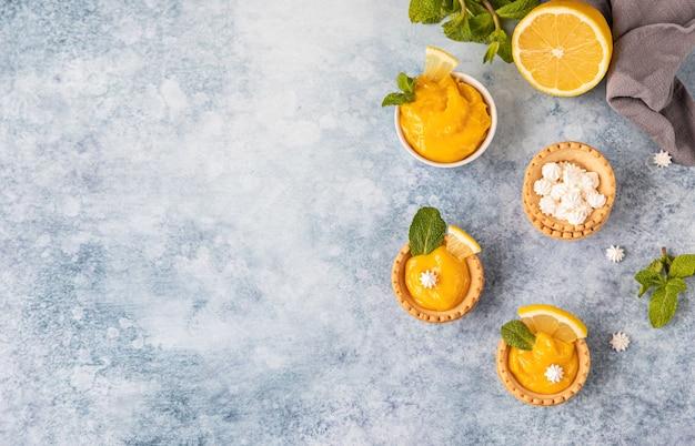 레몬 커드를 곁들인 미니 타르트 미니 머랭 레몬 조각과 민트