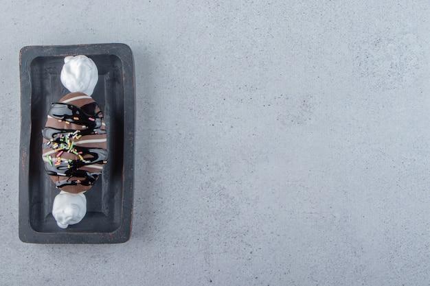 검정 접시에 스프링클이 있는 맛있는 미니 초콜릿 케이크. 고품질 사진