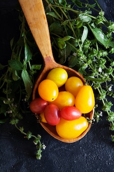 Mini tomatoes on a wooden spoon with sprigs of basil on a dark concrete surface
