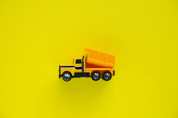 Mini toy dump truck on yellow for vehicle and transportation concept