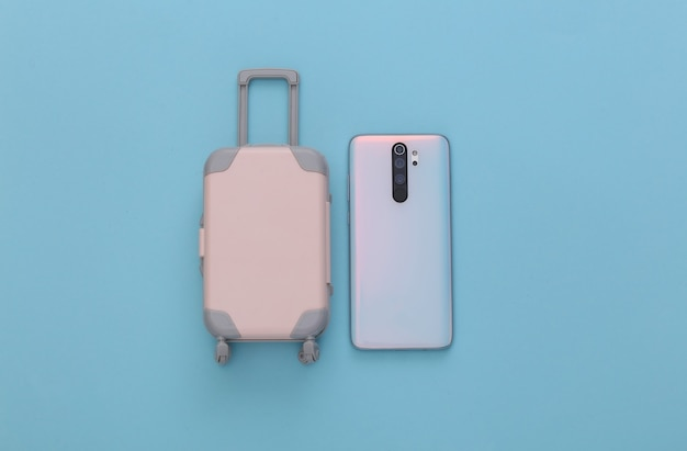Mini toy travel luggage and smartphone on blue