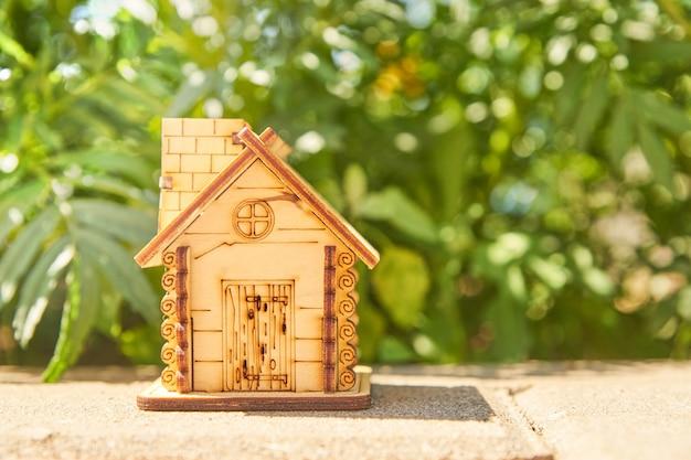 여름 자연 배경에 미니 장난감 목조 주택입니다. 모기지, 건설, 임대, 가족 및 재산 개념으로 사용의 개념. 복사 공간 프리미엄 사진