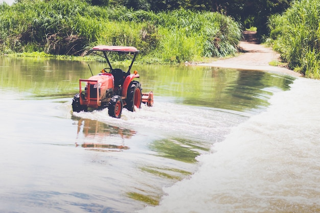 Mini tractor stand in canal for washing