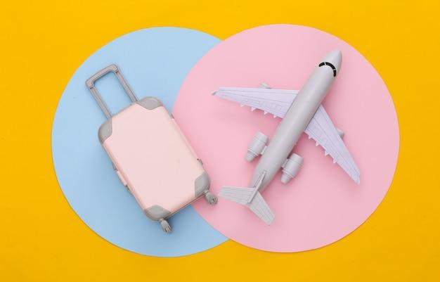Mini travel luggage and air plane. flat lay. minimalism