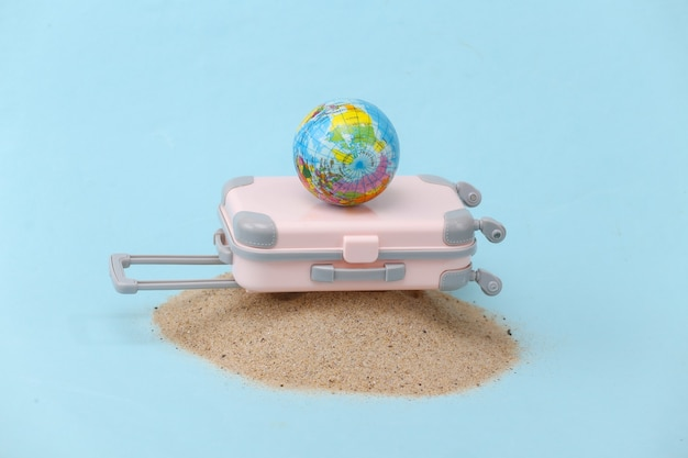 Mini travel luggage suitcase with globe on sand island. travel, beach vacation concept