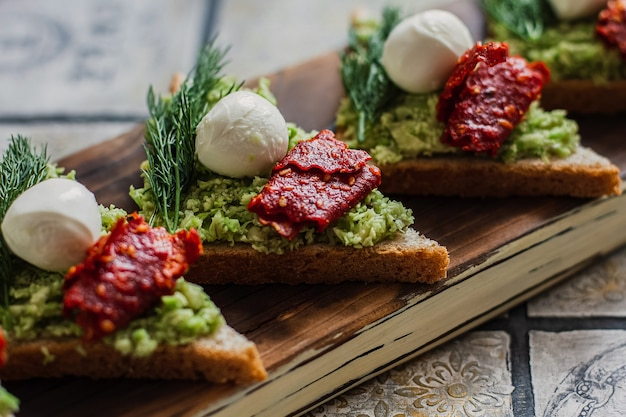 Mini triangle canapes bruschetta with avocado, mozarella and dried tomatos on the rustic board on the vintage tiled background.
