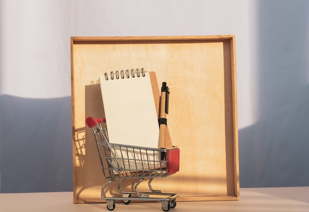 Mini trolley cart with white card casting a shadow on wooden frame