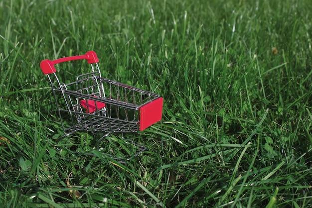 緑の草の背景にミニトロリーショッピングカート。事業投資と不動産のコンセプト。
