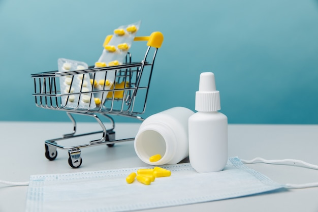 파란색 backround 온라인 쇼핑 개념에 알 약 및 의료 도구와 미니 트롤리