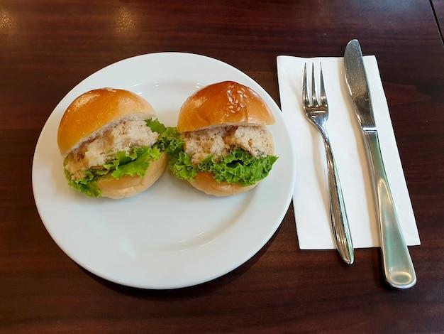 Мини гамбургеры из тунца с салатом из майонеза на белой тарелке и ножевой вилкой на деревянном столе