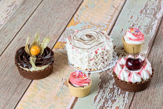 乾燥ココナッツチップとホイップクリームで飾られたミニバニラケーキ。ミニパイとミニサブレペストリーパイの隣。