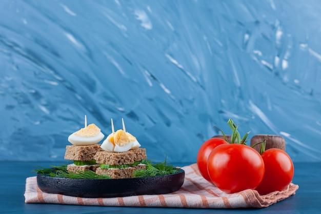 파란색 배경에 차 수건에 보드에 미니 야채와 치즈 샌드위치 꼬치.