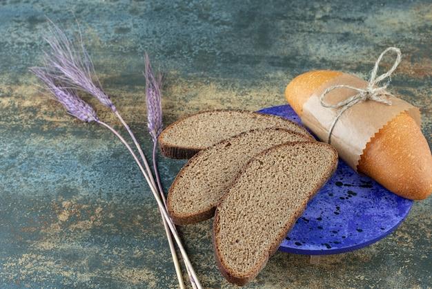 青いプレートに新鮮な茶色のパンのスライスとミニ白パン