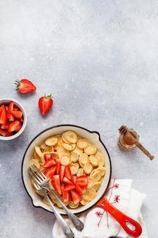 灰色の背景の朝食用フライパンにイチゴとミニ白いパンケーキシリアル。小さなパンケーキとトレンディな家庭の朝食。上面図。