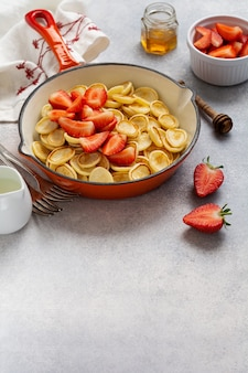 Мини-белые хлопья для блинов с клубникой в сковороде на завтрак на сером фоне.