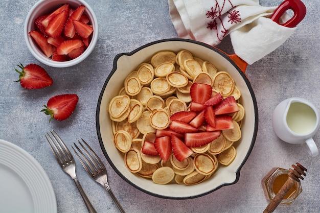 灰色の背景に朝食用フライパンにイチゴとミニ白いパンケーキシリアル