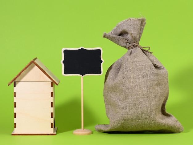 녹색 표면에 미니 목조 목조 주택과 분필 포인터. 부동산 구매 개념, 모기지 및 주택 개조