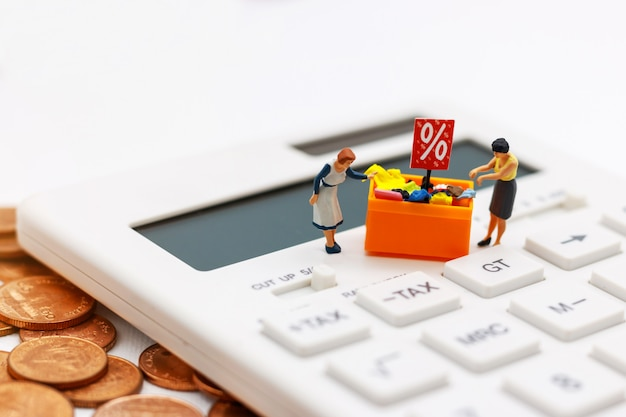 Miniatrue people, shoppers buy goods on sale with discount tray on calculator and coins