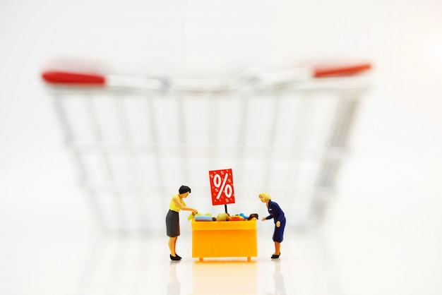 Miniatrue people, shoppers buy goods on sale with discount tray and shopping cart