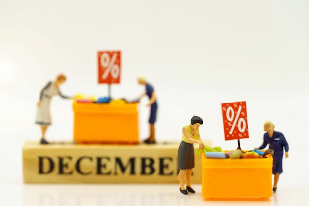 Miniatrue people, shoppers buy goods on sale with discount tray
