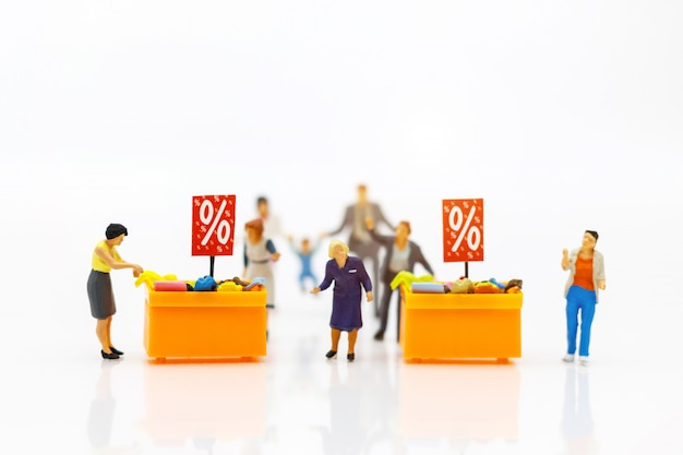 Miniatrue people: shoppers buy goods on sale with discount tray.
