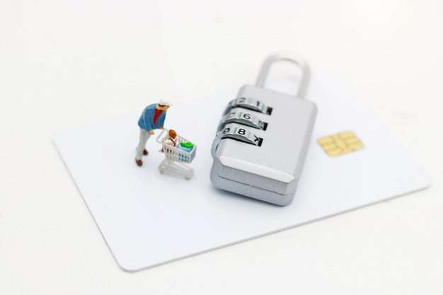 Miniatrue people, shoppers with shopping cart standing  on credit card