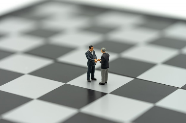 Miniature 2 people businessmen shake hands on a chessboard with a chess piece