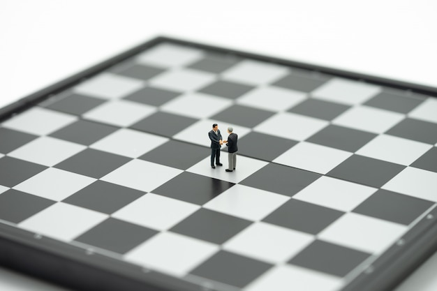 Miniature 2 people businessmen shake hands on a chessboard with a chess