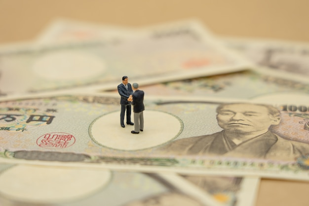 Miniature 2 people businessmen shake hands stand on japanese banknotes worth 10,000 yen